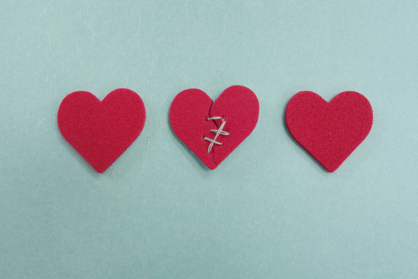 Three red hearts, one broken and stitched, on blue
