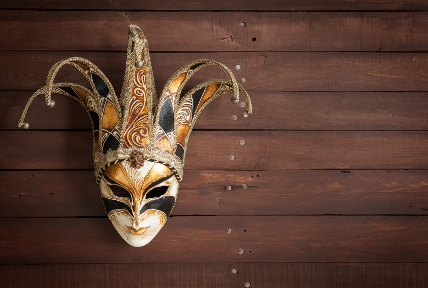 Venetian carnival mask with golden and white hues on a brown wooden background with copy space