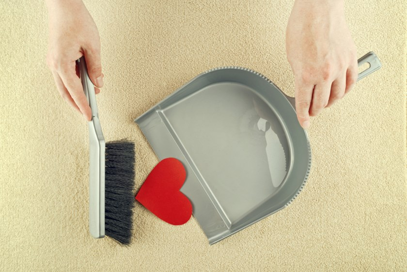 Hand sweeping heart from the floor with brush cleaner.